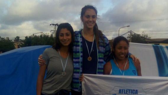 Camila Domínguez junto a Andrea Ubiedo y Victoria Espinoza en el podio de salto en largo.